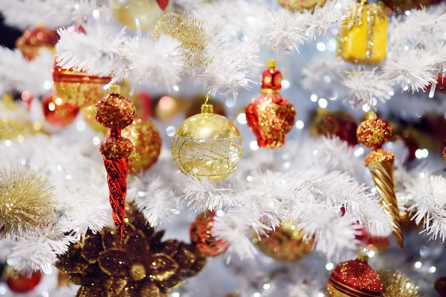 Branch of white artificial christmas tree decorated with gold and red balls. close up.