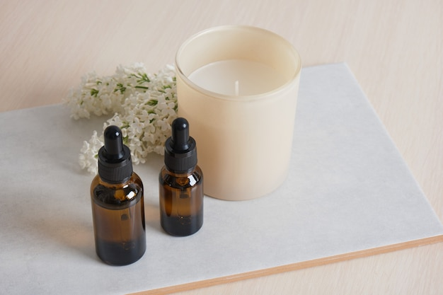 A branch of white lilac, aroma candle in a glass and brown bottles with aroma oil in a ceramic bowl on beige background copy space