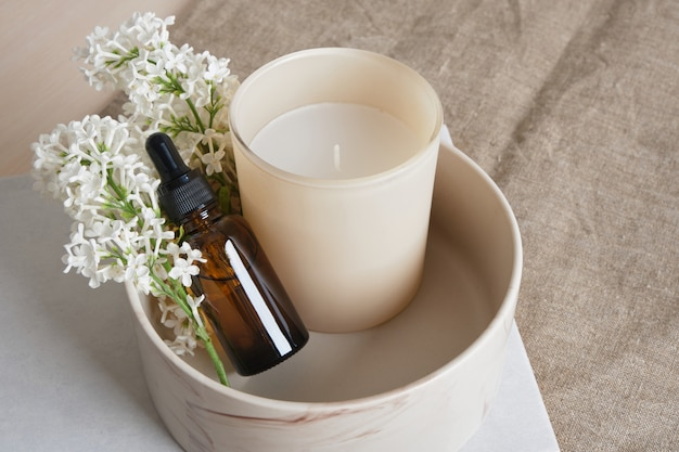 A branch of white lilac, aroma candle in a glass and brown bottles with aroma oil in a ceramic bowl on a natural linen background copy space