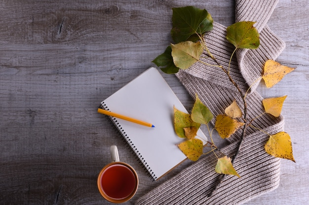 Branch with autumn yellow and green leaves with scarf, notepad and tea on light wooden . autumn composition