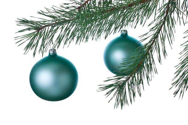 白い背景の上のクリスマスツリーの装飾とブランチ