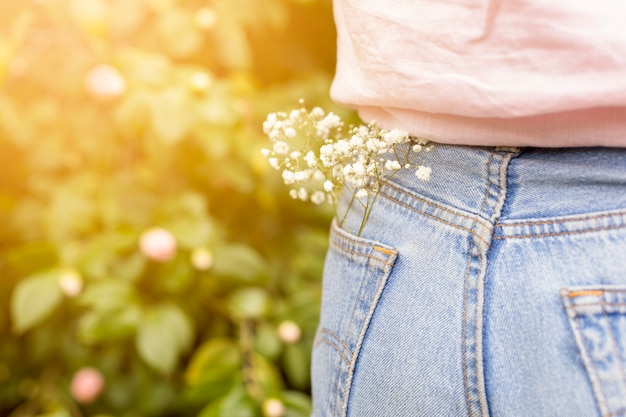 Branch with white flowers placed in back pocket of woman jeans