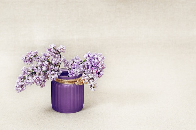 Branches of blooming lilac with vase on blurred background with copy space.