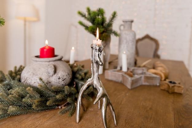 クリスマスの時期、ベリーと緑のbranches.brightly輝くキャンドルでろうそくを燃やします。木製table.preparingのクリスマスキャンドルと組成。手作りの家の装飾。手作りの装飾