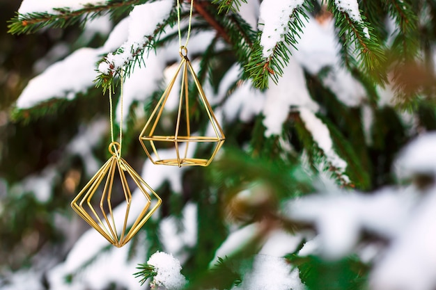 The branches of the christmas tree covered with snow outdoor decorated with gold metal minimalist figures