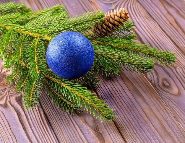Branches of a christmas tree decorated with blue ball with silk on a wooden table