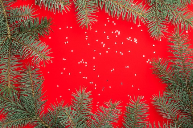 Branches of a christmas tree on red with silver confetti stars. flat lay.