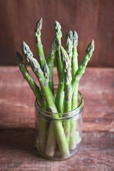 Branches of fresh green asparagus in a jar