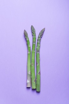 Branches of fresh green asparagus on lilac surface