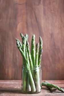 Branches of fresh green asparagus on wooden background