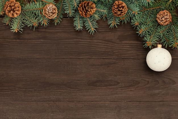 クリスマスツリーの枝と木製のテーブルの上の円錐形。スペースをコピーします。