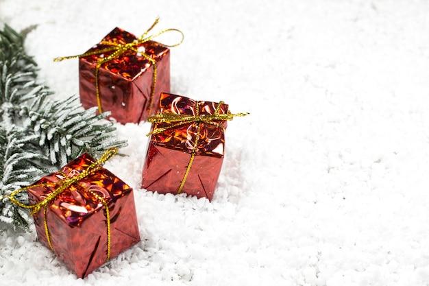 雪の中で赤いボックスにクリスマスツリーと3つの贈り物の枝