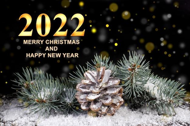 金色のライトと黒の背景に雪の中で円錐形のクリスマスツリーの枝
