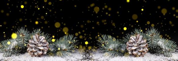 金色のライトと黒の背景に雪の中で松ぼっくりとクリスマスツリーの枝