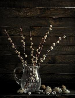 꽃 버드 나무의 가지 배경에 어두운 유리 항아리에 서 프리미엄 사진