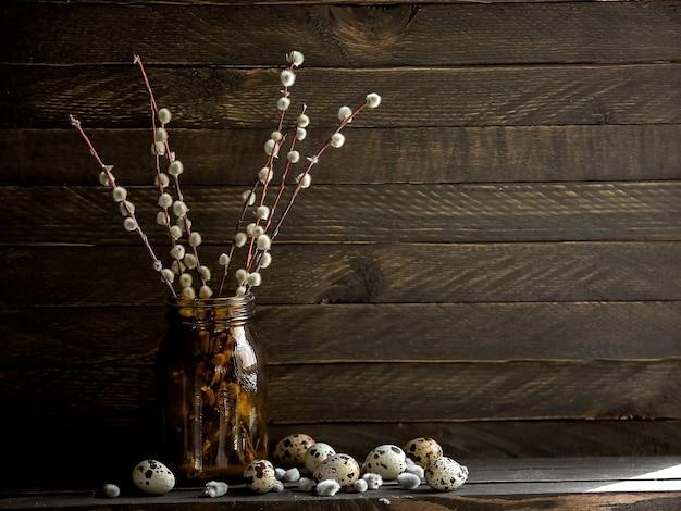 꽃 버드 나무의 가지 배경에 어두운 유리 항아리에 서