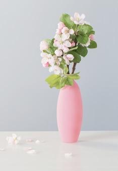 Ветки яблони с цветами в розовой вазе на белом столе