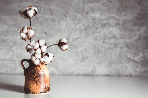 灰色がかった青の壁に茶色の籐の花瓶の綿の枝