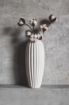 Ветки хлопка в вазе на фоне