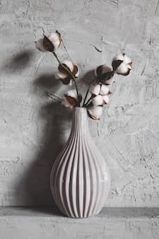 背景の花瓶の綿の枝