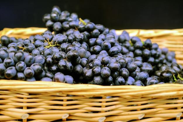 枝編み細工品バスケットのブドウの枝。食料品店で新鮮な熟した赤ぶどうの束