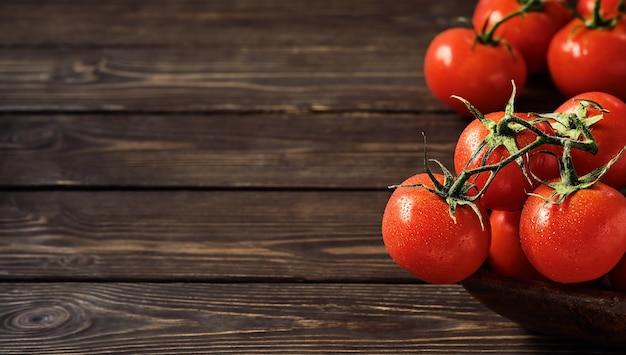 暗い木製の壁に熟したジューシーなトマトの枝。コピースペースのあるフレッシュトマトのクローズアップ。水滴のトマト。