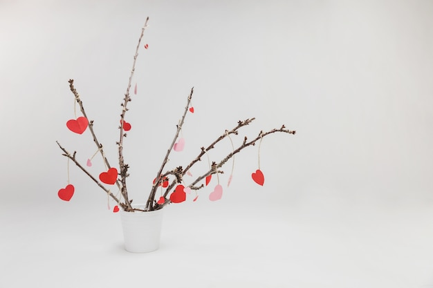 Branches of a plant in a white flowerpot with hanging hearts