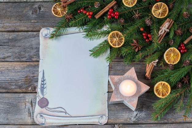 Branches of spruce, cinnamon, anise, lemon slices, red berries, a candle in a candlestick and a sheet of paper
