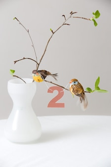 Branches of a tree in a beautiful white vase with birds and number 2 as decoration stylish bouquet