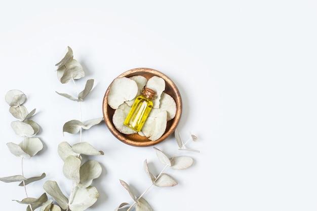 Ветки с листьями эвкалипта и бутылка эфирного масла на виде сверху с копией пространства