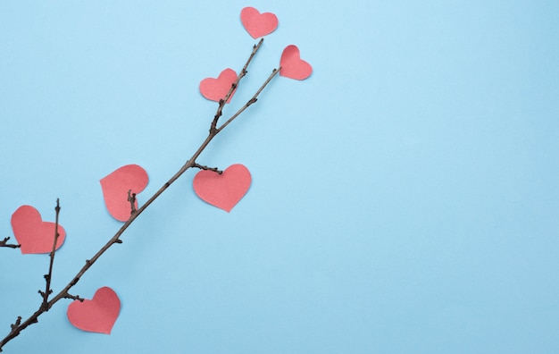 Branches with hearts on blue background with copy space
