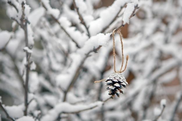 눈과 크리스마스 트리 콘이 있는 지점. 겨울 배경과 자연
