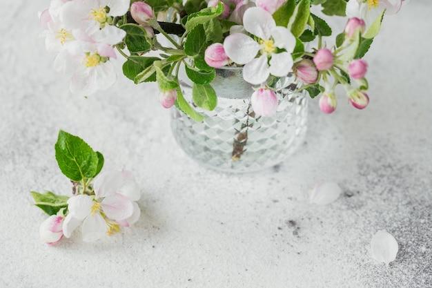 회색 배경에 투명한 유리에 흰색 사과 꽃이 있는 가지. 정물, 부활절 인사말 카드