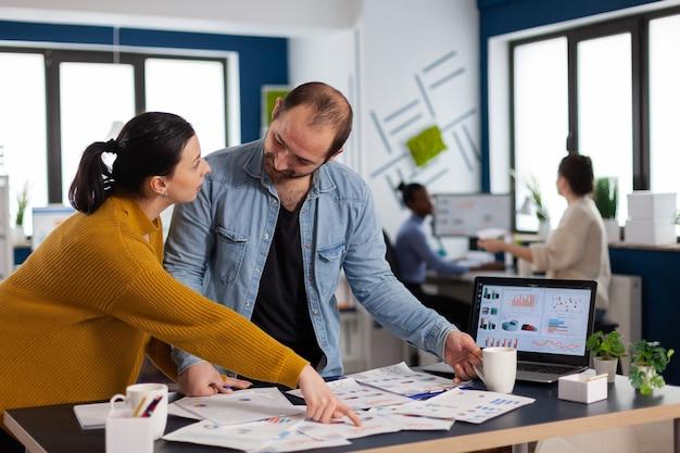 시작 사무실 토론에서 직원에게 설명을 요청하는 브랜드 관리자, 컴퓨터에서 회사 재무 보고서를 분석하는 다양한 비즈니스 팀