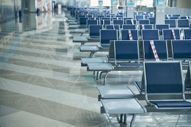 Brand new departure hall at international airport with protective tape on bench