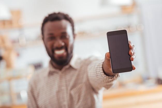 真新しいデバイス。明るく笑顔の若い男性の手にある電話に焦点を当て、彼の新しい購入に満足している