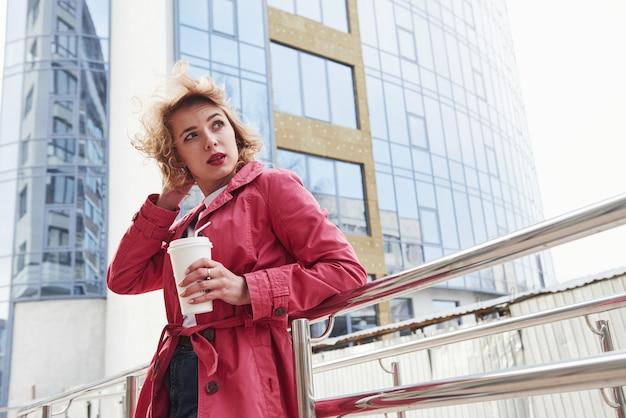 真新しい新鮮な飲み物。暖かい赤いコートを着た大人のきれいな女性が彼女の週末の時間に街を歩いている