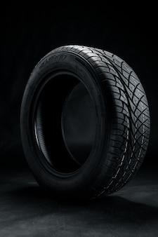 Brand new modern car tyre on a black background