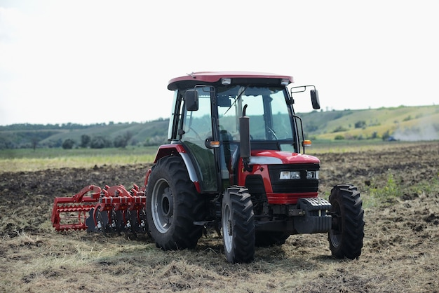 Brand new red tractor on the field working. tractor cultivating soil and preparing a field for planting