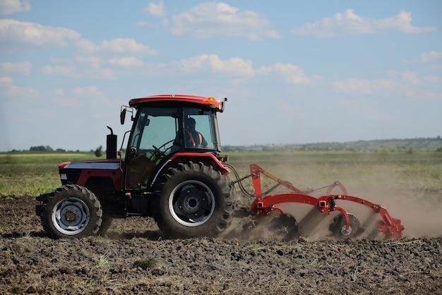 Новый красный трактор на поле работает. трактор возделывает почву и готовит поле к посадке