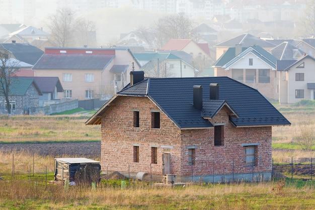 먼 도시의 배경에 교외 이웃에 기와 지붕과 창문 개구부가있는 새로운 넓은 벽돌 2 층 주거용 주택. 건물, 모기지 및 관계 부동산.