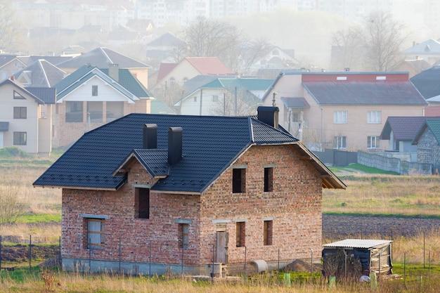 먼 도시 교외 지역에 기와 지붕과 창문 개구부가있는 새로운 넓은 벽돌 2 층 주거용 주택. 건물, 모기지 및 부동산.