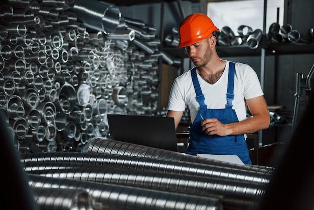 Новенькие вентиляционные трубы. мужчина в военной форме работает на производстве. современные промышленные технологии.