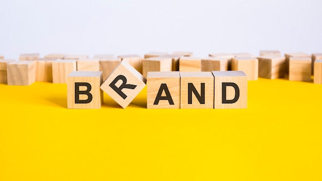 Brand word is made of wooden building blocks lying on the yellow table, concept