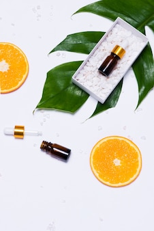 Макет брендинга. натуральное эфирное масло, косметические флаконы с дольками апельсина.