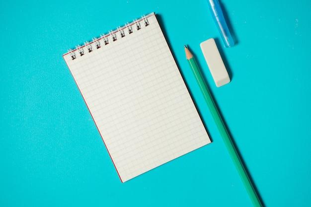 Брендинг макет с ручкой, карандашом, ластиком и небольшой блокнот, изолированных на синем фоне. копировать пространство вид сверху. изометрическая концепция. школьные принадлежности