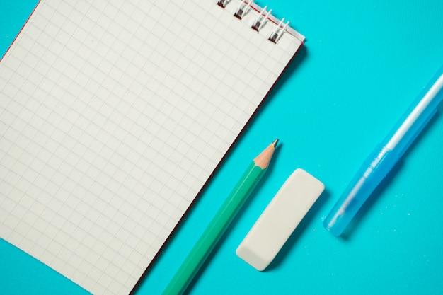 ペン、鉛筆、消しゴム、青い背景に分離された小さなノートでモックアップをブランディング。コピースペース。上面図。等尺性の概念。学用品