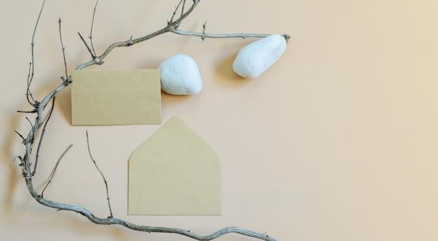 중립 베이지 색 배경에 자연 요소로 봉투 빈, 흰 돌 및 마른 나무 브런치가있는 브랜딩 모형 템플릿. 복사 공간, 평면도, 최신 유행 디자인 배너 사진.