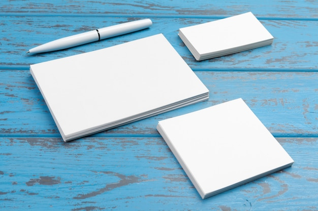 Branding stationery  on blue desk. top view of paper, business card, pad, pens and coffee.