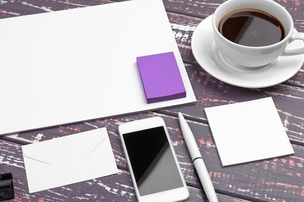 Branding stationery mockup on purple desk. top view of paper,  business card, pad, pens and coffee.